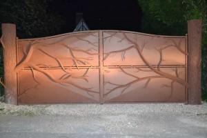 portail arbre de nuit, les piliers forment les troncs, les vantaux accueillent les branches